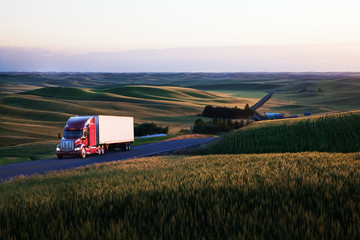 Commercial truck driving on road passing through wheat fields Wall mural