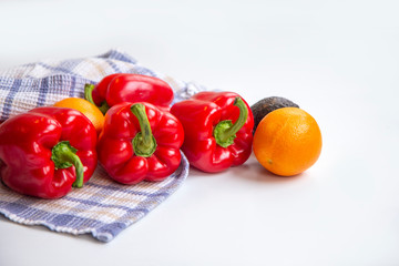 Sweet peppers, oranges and avocado in a tea towel on a white table