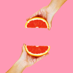 Grapefruit in hand on a bright background. Modern art collage