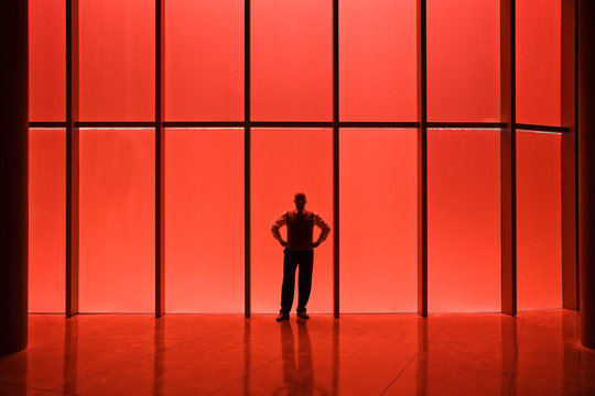 Businessman standing near red tinted window in office lobby