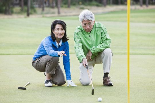 Senior couple observing golf ball on golf course