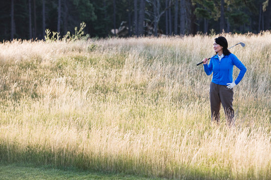 Senior woman with golf club standing in grassy field