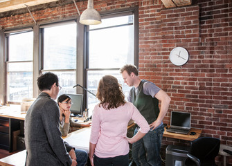 Business people taking over blueprint in office