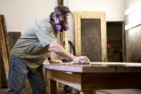 Factory worker applying finish stain on table in workshop