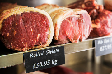 Close up of piece of rolled beef sirloin meat on metal shelf