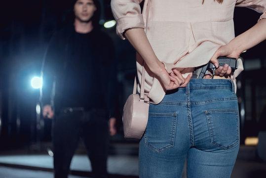 back view of woman hiding gun behind back near thief at night