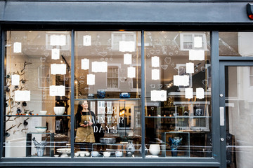Woman standing in pottery shop seen through window