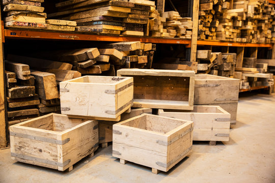 Shelves with wooden planks and stack of wooden crates in warehouse