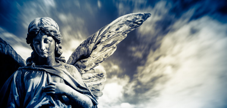 Guardian angel sculpture with open long wings isolated with blurred white clouds dramatic light blue sky. Angel sad expression sculpture with eyes down and hand in front of chest.
