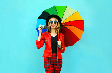 Happy smiling woman holding colorful umbrella, retro camera taking picture in red jacket, black hat on blue wall background