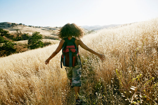 Rear view of young woman with backpack hiking in field