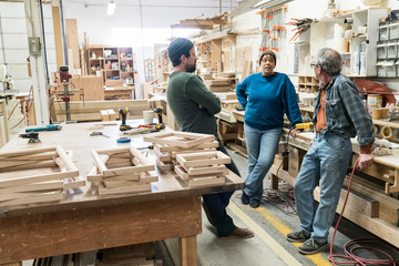 Carpenters talking with each other in workshop