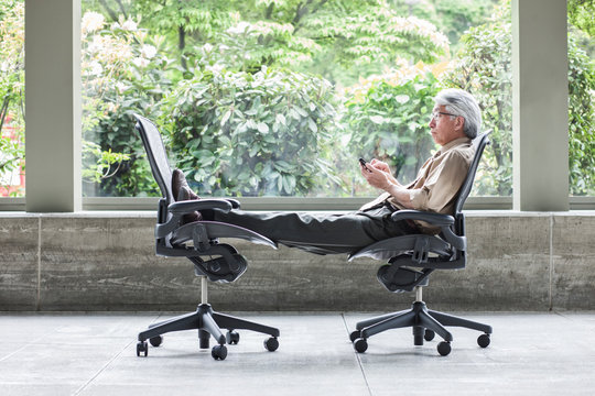 Side view of businessman using smartphone on chair