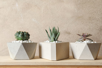 Beautiful succulent plants in stylish flowerpots on wooden table against brown background. Home...