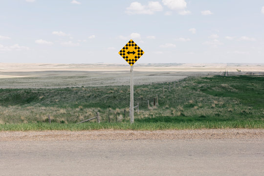 View of arrow intersection sign on rural farmland
