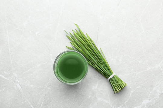 Glass of wheat grass juice and green sprouts on grey marble table, flat lay