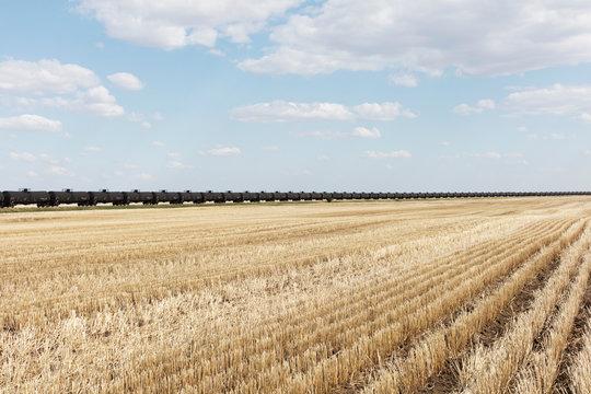 View of oil train cars passing through farmland