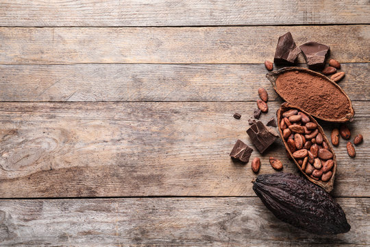 Flat lay composition with cocoa pods and beans on wooden table. Space for text