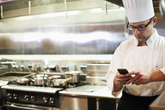 Chef using smartphone in commercial kitchen