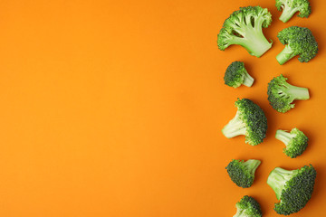 Flat lay composition with fresh green broccoli on color background. Space for text