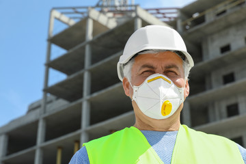 Professional builder in safety equipment at construction site, space for text