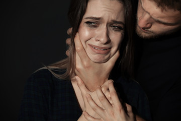 Man abusing young woman on dark background. Stop sexual assault - fototapety na wymiar