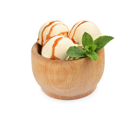Delicious ice cream with caramel sauce and mint in wooden bowl on white background