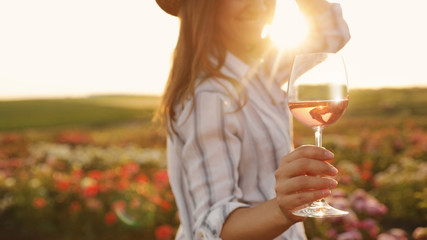 Woman with glass of wine in rose garden on sunny day, closeup Wall mural