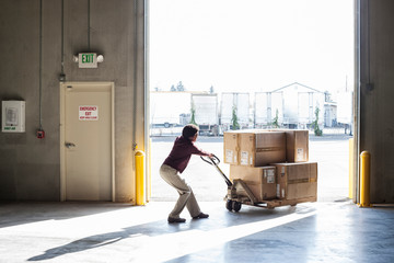 Worker using pallet jack in warehouse