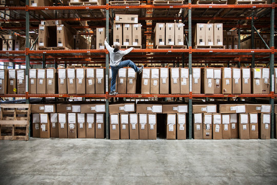 Worker trying to climb rack of products in warehouse