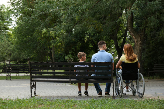 Woman in wheelchair with her family at park