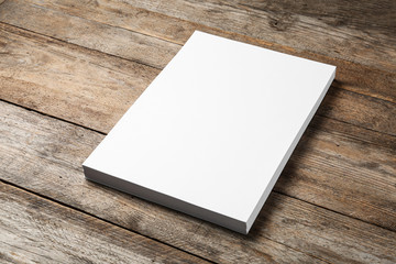 Stack of blank paper sheets for brochure on wooden background. Mock up