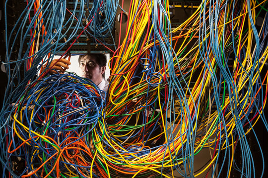 Technician working on tangled mess of cat 5 cables in server room