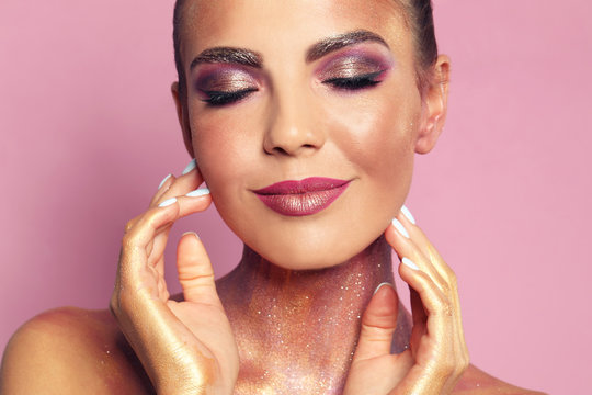 Sexy young woman with glitter makeup on pink background