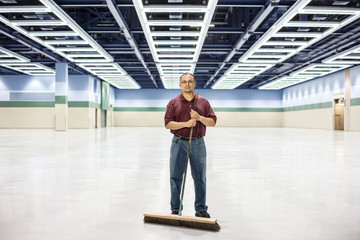 Portrait of man standing with broom at convention center