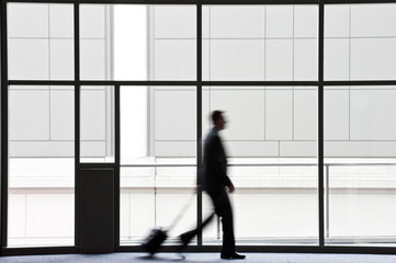 Side view of businessman with luggage walking by window in convention center