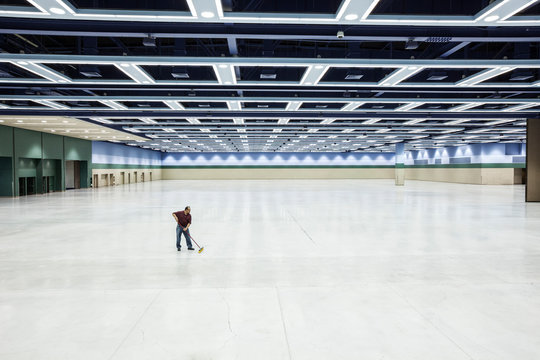 Worker sweeping floor of convention center