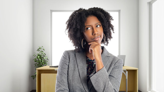 Black African American businesswoman in an office thinking of ideas.  She is an owner or an executive of the workplace.  Depicts careers and startup business.