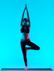 one caucasian woman exercising tree pose Vriksasana yoga exercices in silhouette studio isolated on...