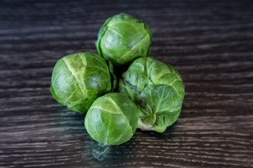 Keuken foto achterwand Brussel Rustic, organic, healthy brussel sprouts. Home grown and displayed on a dark wood grain bench. Dark green leafy outer, white and creamy inside. Brassica high in vitamins C, B and K, good for winter.
