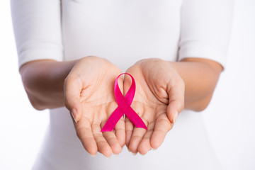 womans hands holding pink breast cancer awareness ribbon on white background. healthcare and medicine concept.
