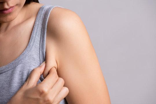 Close up woman pulling her skin underarm. problem armpit fat skin concept.