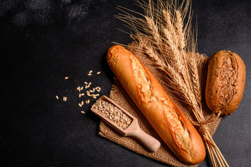 Foto op Aluminium Brood Fresh fragrant bread with grains and cones of wheat against a dark background. Assortment of baked bread on wooden table background