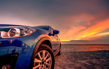 Blue compact SUV car with sport and modern design parked by beach at sunset. Hybrid and electric car technology. Car parking space. Automotive industry. Car care business background. Beautiful sky.