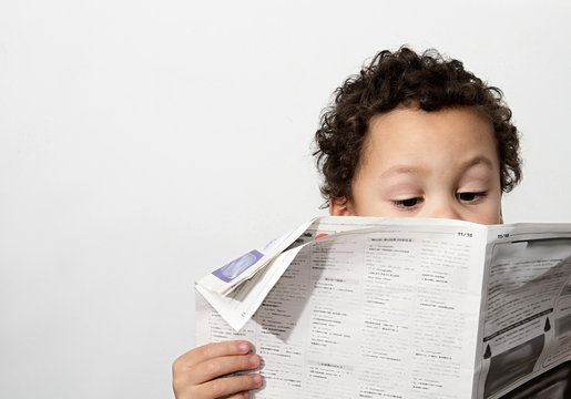 Little boy reading newspaper and smiling in the morning been educated with white background stock image and stock photo