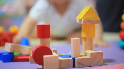 baby playing analogue colorful wooden toy. creative play for children brain development. image focus on toys and baby sitting out of focus in the background.
