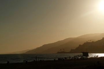 People walk at sunset at Will Rogers State Beach in Pacific Palisades