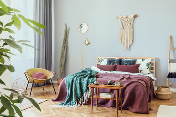 Stylish and luxury interior of bedroom with design furnitures, honey yellow armchair, gray macrame on the walls and elegant accessories. Beautiful bed sheets, blankets and pillows. Warm home decor.