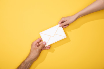 cropped view of man and woman holding paper icon of white envelope on yellow