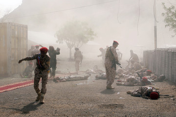 Soldiers lie on the ground after a missile attack on a military parade during a graduation ceremony for newly recruited troopers in Aden, Yemen